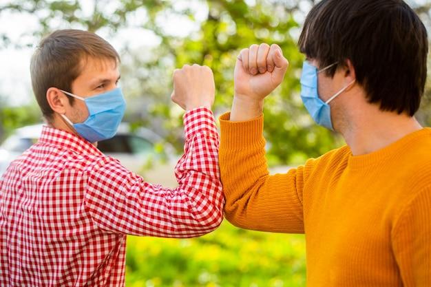 Masque médical d'amis. les coudes se cognent.