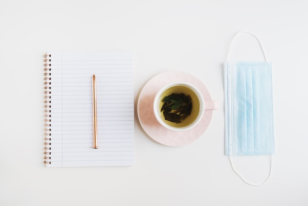 Masque médical au thé vert dans une tasse rose et un cahier avec un stylo en métal sur une table blanche à plat