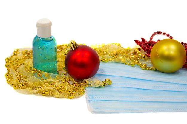 Masque médical bleu à côté des décorations de noël sur fond blanc. arbres de noël, ballons, humeur du nouvel an et protection respiratoire