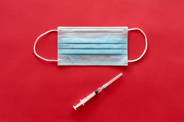Masque médical bleu pour éviter le coronavirus et la seringue.
