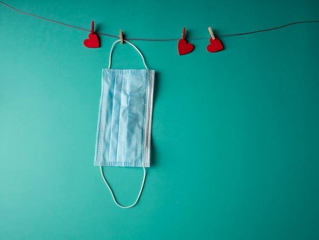 Un masque médical bleu qui pèse sur une corde avec trois coeurs rouges fixés avec des pinces à linge sur fond vert