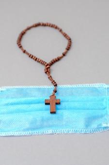 Masque médical et chapelet en bois avec croix.