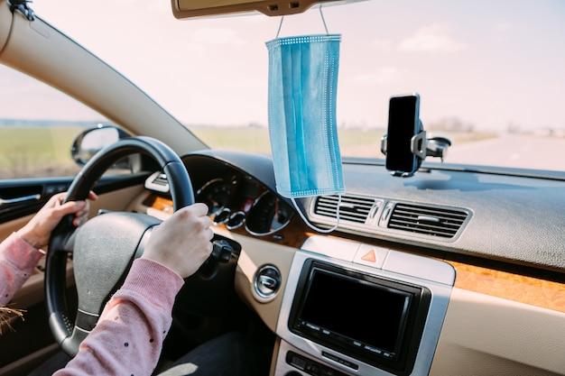Masque médical dans la voiture sur le panneau