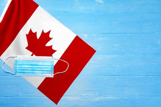 Masque médical sur le drapeau du canada sur planche de bois close up