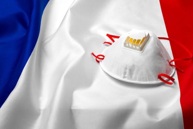 Masque médical sur le drapeau national de la france sur planche de bois