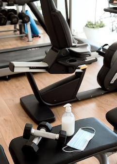 Masque médical sur l'équipement de gym avec des poids