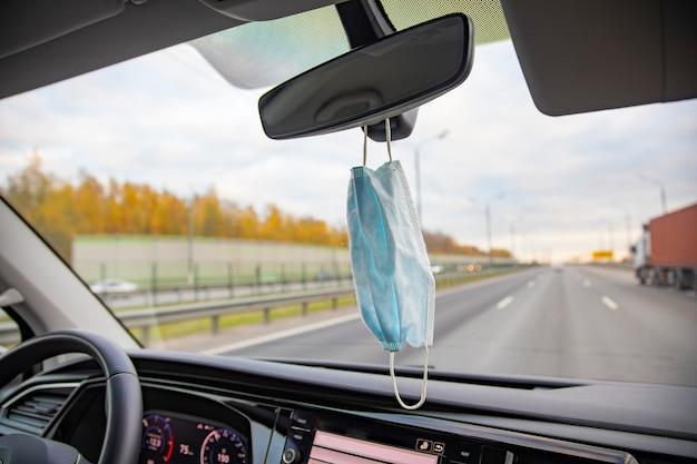 Un masque médical est suspendu au rétroviseur du salon dans la voiture sur l'autoroute. fermer