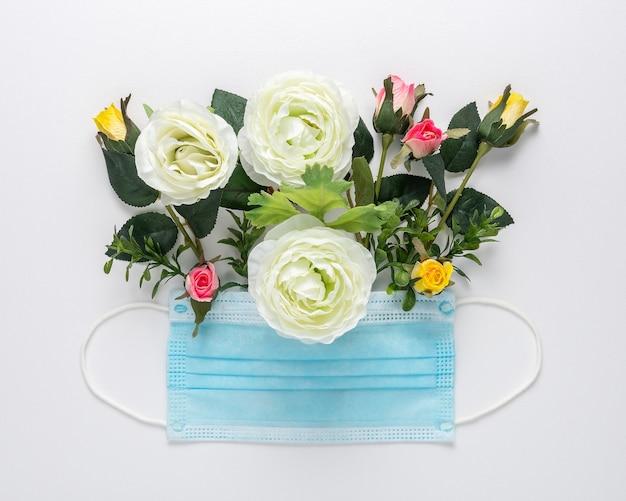 Masque médical avec des fleurs de couleurs différentes sur une surface blanche.