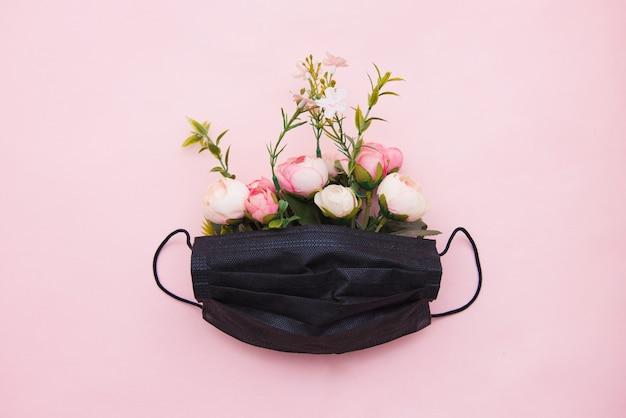 Masque médical avec des fleurs sur fond rose