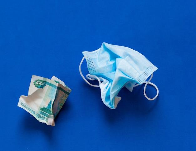 Masque médical froissé contre le coronovirus et argent russe froissé sur fond bleu.