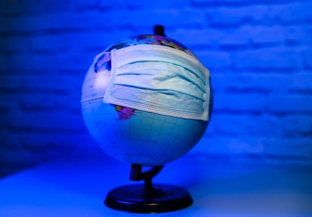 Masque médical sur globe contre un virus