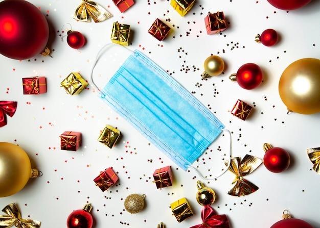 Masque médical avec des jouets de noël sur fond blanc avec des confettis