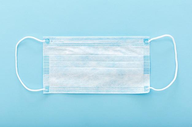 Masque médical, masque de protection médical sur fond bleu. le masque facial chirurgical jetable couvre la bouche et le nez pour les soins de santé