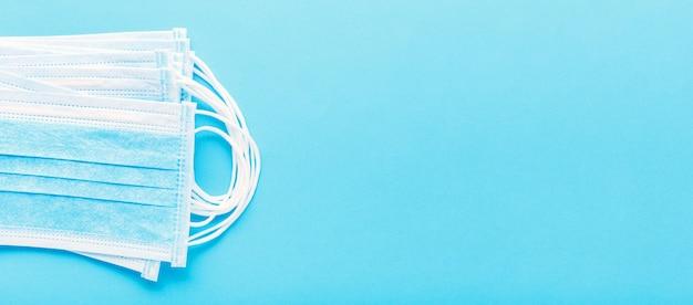 Masque médical, masques de protection médicale sur fond bleu. un masque facial chirurgical jetable couvre la bouche et le nez. concept de soins de santé et médical. bannière web longue coronavirus covid-19 concept
