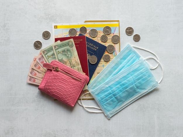 Un masque médical, un passeport et de l'argent des dirhams sont disposés sur la table