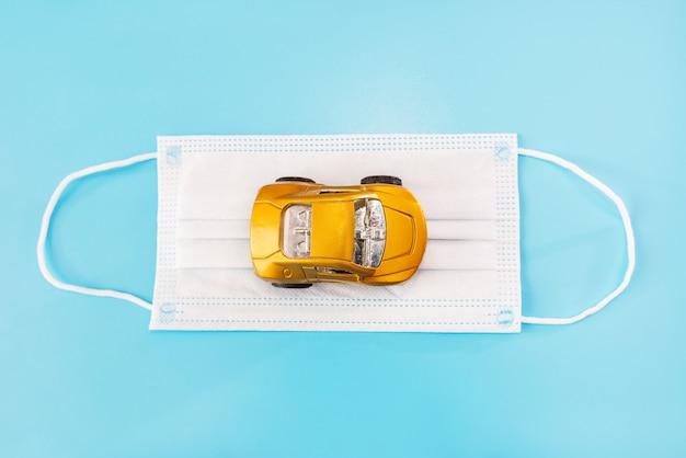 Masque médical et petite voiture sur fond bleu. vue d'en-haut.