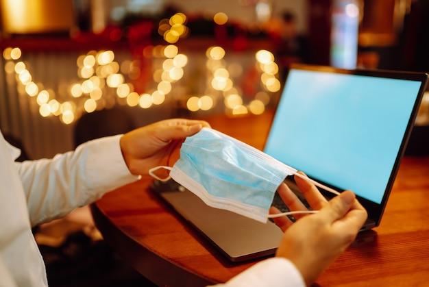 Masque médical stérile de protection dans la main masculine. travail à distance pendant les vacances d'hiver.