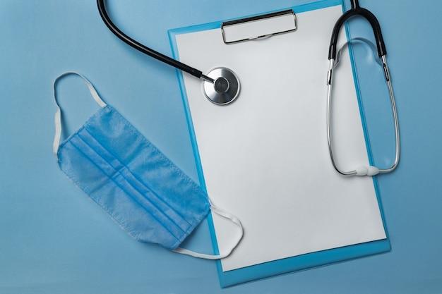 Masque médical, stéthoscope et document vierge sur fond bleu.