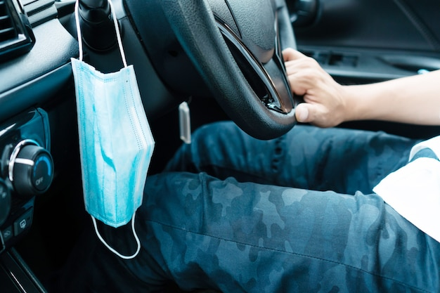 Masque médical suspendu dans la voiture pour réduire la transmission