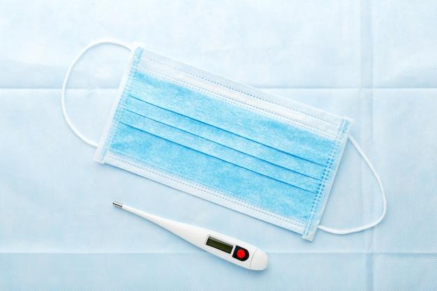 Masque médical, thermomètre, contrôle de la fièvre pour mesurer la température corporelle. diagnostic du coronovirus covid-19 masque de protection facial chirurgical sur fond bleu. concept médical de la santé. arrêtez le virus sars-cov-2