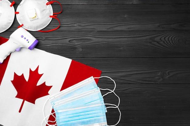 Masque médical et thermomètre sans contact sur le drapeau du canada sur planche de bois