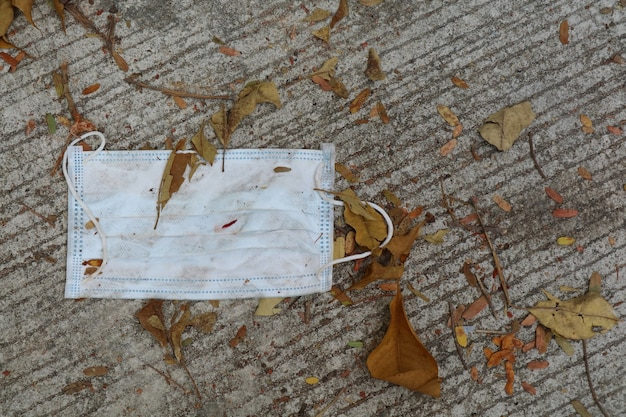 Masque médical usagé jeté sur le sol en béton.