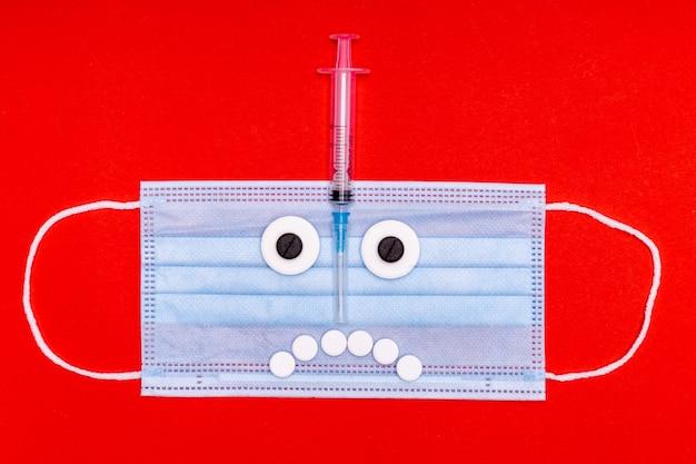 Masque médical avec un visage fait de pilules et d'une seringue sur fond rouge