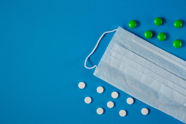 Masque médical sur le visage et pilules sur la table bleue d'en haut