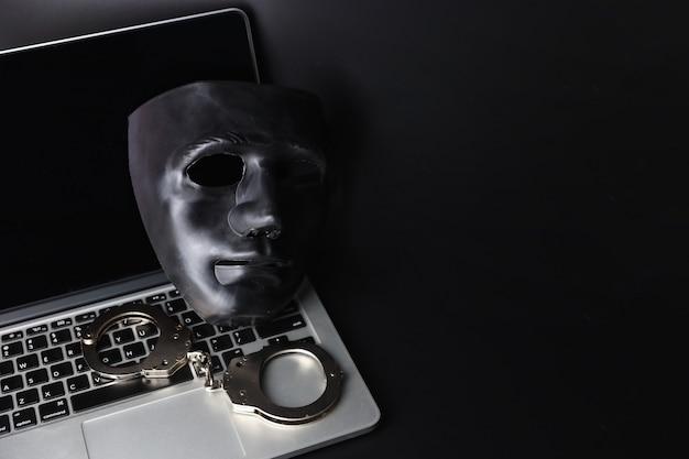 Masque noir et menottes sur ordinateur sur fond noir