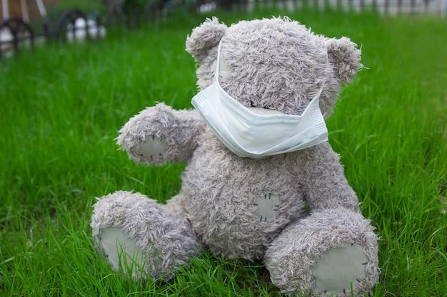 Masque sur un ours en peluche sur une herbe