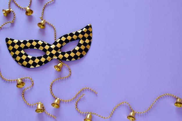 Masque et perles avec des cloches sur fond violet sur le côté gauche. disposition à plat