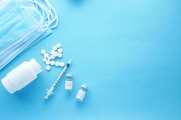 Masque de pilules médicales de vaccin contre le coronavirus et seringue sur surface bleue