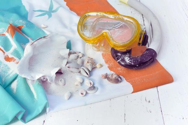 Masque de plongée avec des coquillages exotiques sur une serviette de bain