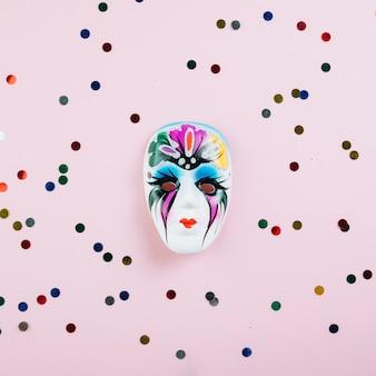 Masque de plume de carnaval avec du matériel de décoration de fête sur fond rose