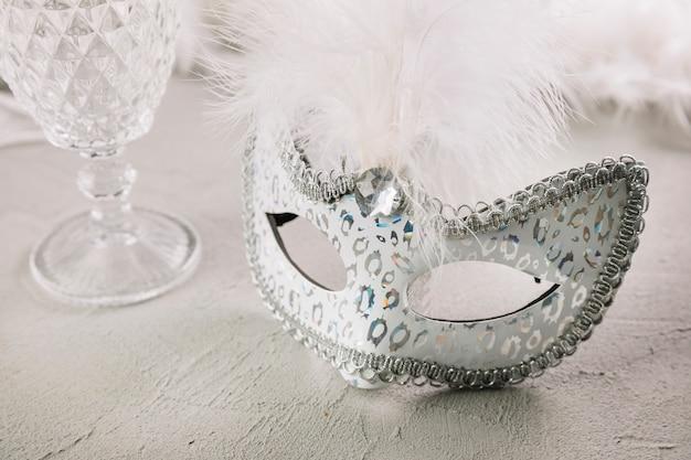 Masque de plume de carnaval mascarade avec verre vide sur fond de béton