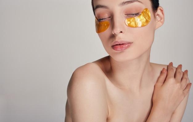 Masque pour éliminer les rides, les cernes. une femme prend soin d'une peau délicate autour de ses yeux. procédures cosmétiques.