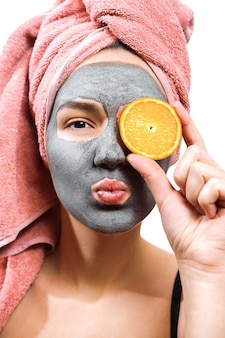 Masque pour femme de peau, fille heureuse et drôle fait un masque pour la peau du visage, la fille ferme les yeux avec de l'orange et envoie un baiser aérien dans l'appareil photo, photo isolée
