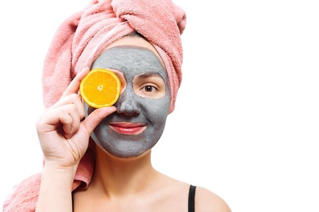 Masque pour la peau femme, fille heureuse et drôle fait un masque pour la peau du visage, la fille ferme les yeux avec de l'orange, la fille sourit, photo isolée