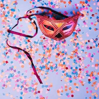 Masque pour les yeux carnival avec des confettis multicolores au-dessus de la toile de fond bleue