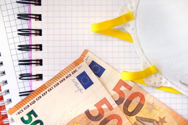 Masque de protection et 50 billets en euros sur un cahier de papier blanc