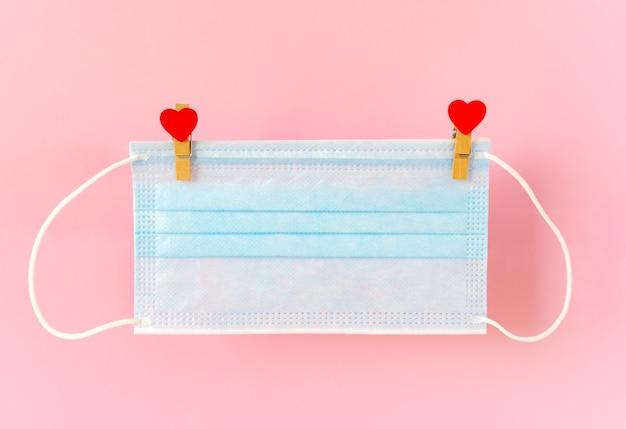 Masque de protection blu suspendu à des pinces à linge avec des coeurs sur une corde.