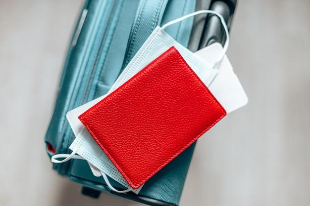 Masque de protection contre le virus corona, passeport, billet et valise pour voyager pendant la pandémie de covid-19.