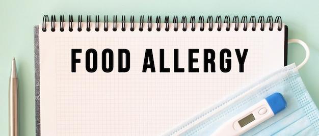 Un masque de protection médicale et un thermomètre se trouvent sur le bloc-notes. texte d'allergie alimentaire dans un cahier.
