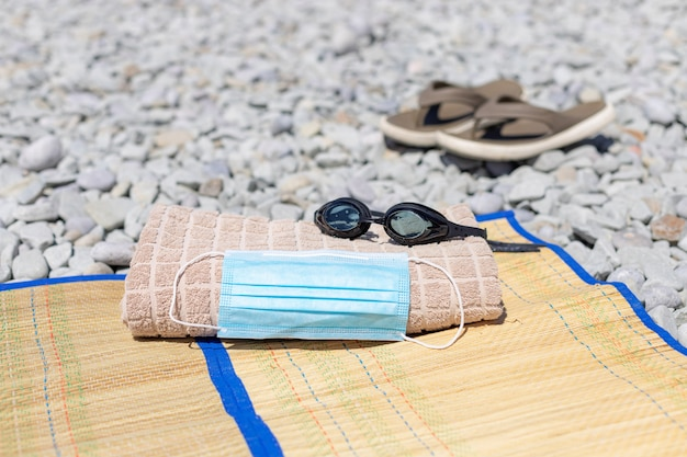 Masque de protection, serviette de plage, lunettes de natation sur la plage.