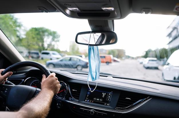 Masque de protection suspendu à un rétroviseur de voiture