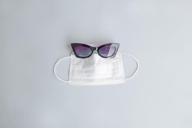 Masque respiratoire et lunettes de soleil sur un espace gris