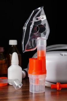 Masque respiratoire pour nébuliseur à compresseur avec différents équipements médicaux pour la thérapie par inhalation pour l'asthme et les maladies respiratoires sur table, mise au point sélective.