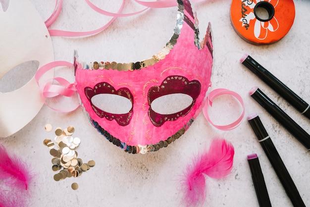 Masque rose à la main sur la table