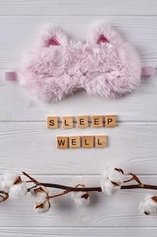 Masque de sommeil en fourrure et branche de saule. concept de bien dormir à plat.