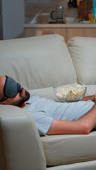 Masque de sommeil pour les yeux de l'homme s'endormir en regardant un film